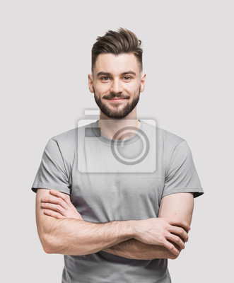 Naklejka Portrait of handsome smiling young man with folded arms. Smiling joyful cheerful men with crossed hands studio shot. Isolated on gray background