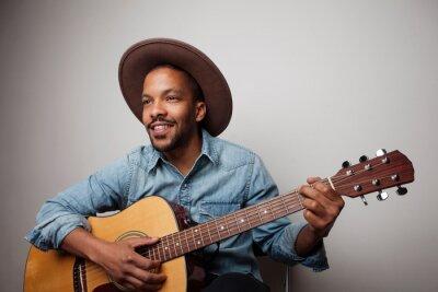 Naklejka Portrait of happy bearded black man playing guitar isolated on white background.