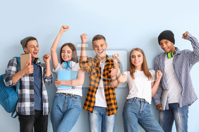 Naklejka Portrait of happy young students on color background