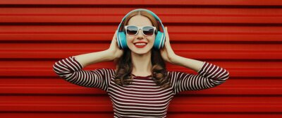 Naklejka Portrait of happy young woman with wireless headphones listening to music on a red background
