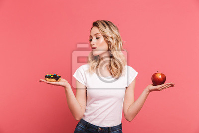 Naklejka Portrait of hesitating blond woman 20s wearing casual t-shirt holding sweet donut and fresh healthy apple