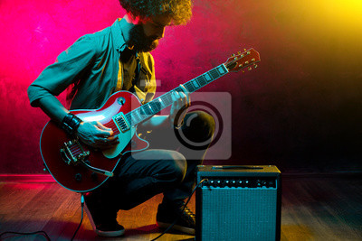 Naklejka Portrait of hipster man with curly hair with red guitar in neon lights. Rock musician is playing electrical guitar.