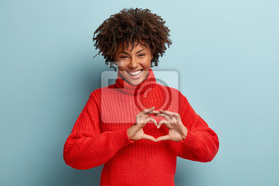 Naklejka Portrait of lovely female model makes heart gesture, says be my valentine, demonstrates love sign, has glad expression, wears warm red jumper, isolated against blue background. Body language