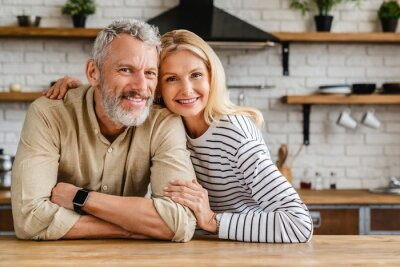 Naklejka Portrait of middle aged couple hugging while standing together in kitchen at home