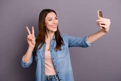 Naklejka Portrait of positive cheerful woman take selfie on her cellphone have video call feel content make v-signs on her vacation holidays, wear denim jeans clothes isolated over grey color background