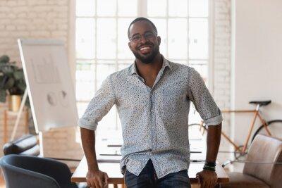 Naklejka Portrait of smiling african American employee posing in office