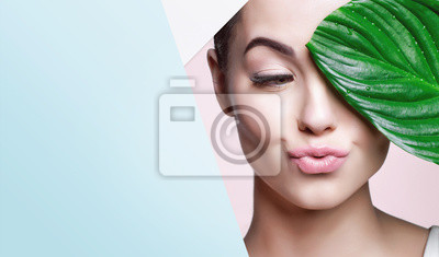 Naklejka Portrait of young beautiful woman with healthy glow perfect smooth skin holds green tropical leaf, look into the hole of colored paper. Model with natural nude make up. Fashion, beauty, skincare.