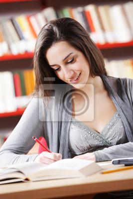 Portret dziewczyna studentów studiuje w bibliotece