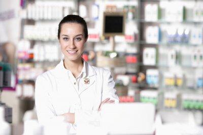 Portret młodego pracownika opieki zdrowotnej i tła aptece.