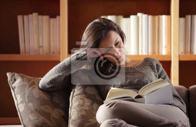 Portret młodej kobiety leżącej na kanapie z książką