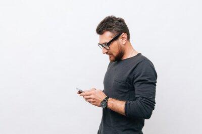 Naklejka Portret młody przystojny mężczyzna używa smartphone nad białym tłem