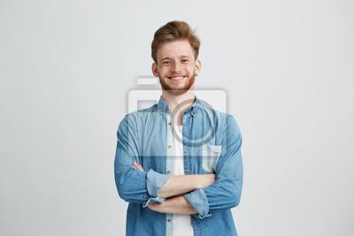Naklejka Portret młody przystojny mężczyzna w cajgowej koszulowej uśmiechniętej patrzeje kamerze z krzyżować rękami nad białym tłem.