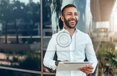 Naklejka Portret młody ufny uśmiechnięty indyjski mężczyzna trzyma pastylkę i patrzeje w odległość