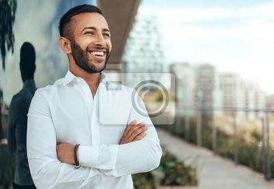 Naklejka Portret młody ufny uśmiechnięty indyjski mężczyzna z jego rękami krzyżował patrzeć w odległość