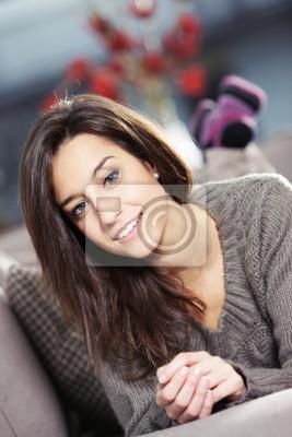 Naklejka Portret pięknej młodej kobiety leżącej na kanapie