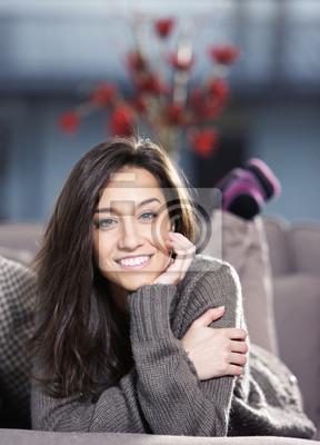 Portret pięknej młodej kobiety leżącej na kanapie