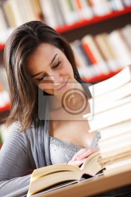 Portret poważne młody uczeń czyta książkę w bibliotece
