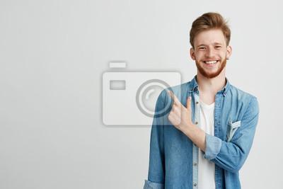 Naklejka Portret rozochocony młody człowiek uśmiecha się patrzejący kamerę wskazuje palec up nad białym tłem.