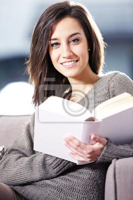 Portret szczęśliwa młoda kobieta, leżąc na kanapie z książką