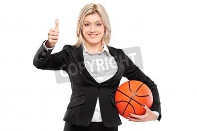 Naklejka Portret szczęśliwy businesswoman gospodarstwa koszykówki i dając kciuki do góry na białym tle