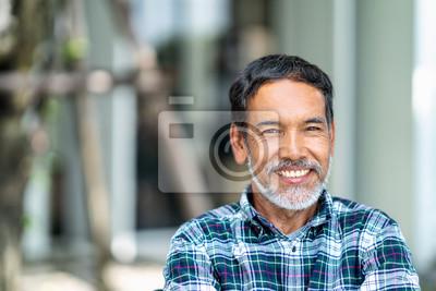 Naklejka Portret szczęśliwy dojrzały mężczyzna z białą, szarą elegancką krótką brodą patrzeje kamerę plenerową. Przypadkowy styl życia emerytów latynoscy ludzie lub dorosły azjatykci mężczyzna uśmiech z ufnym