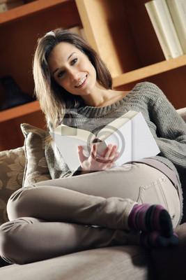 Portret szczęśliwy młoda kobieta leżącego na kanapie z książką