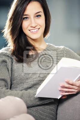 Naklejka Portret szczęśliwy młoda kobieta leżącego na kanapie z książką