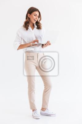 Naklejka Portret urocza uśmiechnięta kobieta z długim brown włosianym mieniem i patrzeć srebnego laptop, odizolowywającego nad białym tłem w studiu