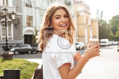 Naklejka Portret uśmiechnięta europejska kobieta spaceruje przez miasto ulicy z srebnym laptopem i takeaway kawa w rękach
