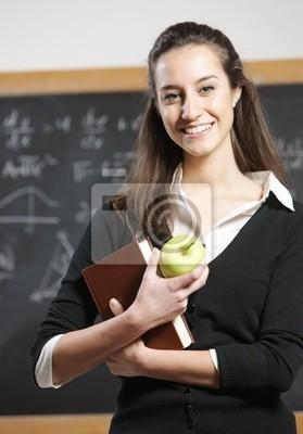 Portret uśmiechniętego studenta z jabłkiem z przodu blackboa