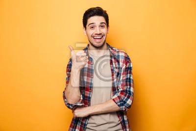 Naklejka Portret uśmiechnięty młody człowiek wskazuje palcowy daleko od