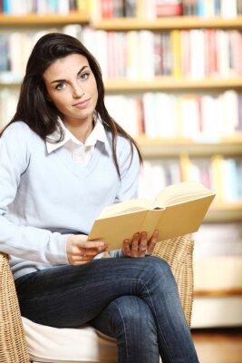 Portret wdzięku studentka z książką w ręce patrząc