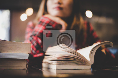 Naklejka Posiedzenie Hipster kobieta nastolatek lektura książki w kawiarni.