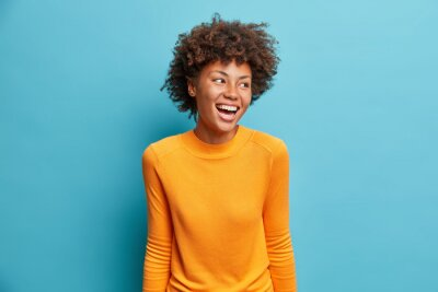 Naklejka Positive cheerful young African American woman laughs positively and looks aside concentrated happily dressed in casual orange jumper isolated on blue studio background. People emotions concept