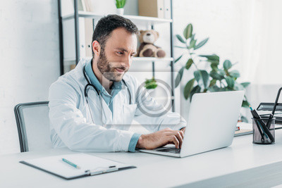 Naklejka positive doctor sitting at workplace and using laptop