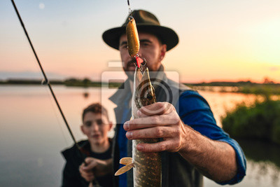 Naklejka Positive man with teenager boy standing together and showing catch fish outdoors