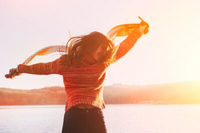 Naklejka Pozytywne młoda dziewczyna ma na sobie ciepłe ubrania zimowe zabawę w jeziorze.