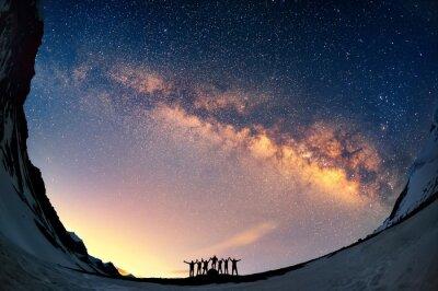 Naklejka Praca zespołowa i wsparcie. Grupa ludzi stoją razem trzymając się za ręce na tle Drogi Mlecznej w górach.