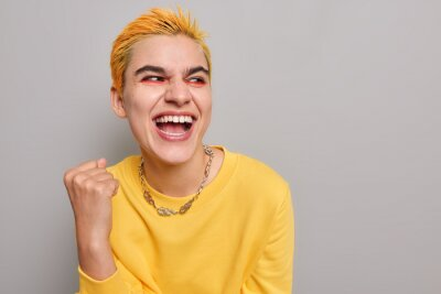 Naklejka Pretty optimistic punk girl feels like winner celebrates success clenches fist looks happily away wears casual yellow jumper isolated on grey background blank copy space belongs to youth subculture