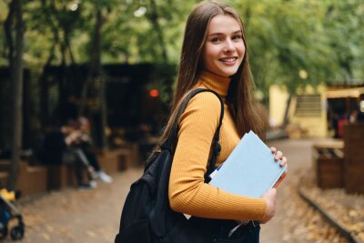 Naklejka Pretty smiling casual student girl with books happily looking in camera in park