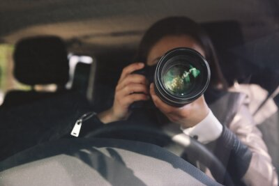 Naklejka Private detective with camera spying from car