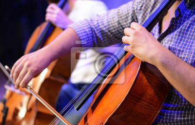 Naklejka Professional cello player's hands close up, he is performing with string section of the symphony orchestra