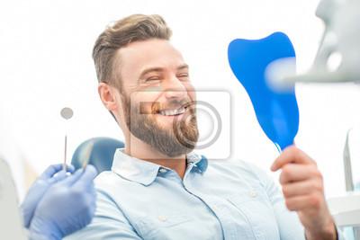 Naklejka Przystojny mężczyzna pacjenta patrząc na jego piękny uśmiech siedzi w stomatologii biura