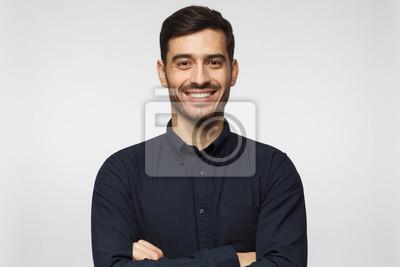 Naklejka Przystojny uśmiechnięty biznesowy mężczyzna w błękitnej koszula odizolowywającej na szarym tle