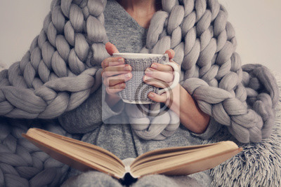 Naklejka Przytulne kobiety pokryte ciepłym miękkim kocem z wełny merynosa czytając książkę. Relaks, komfortowy styl życia.