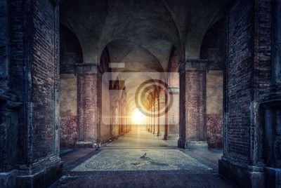 Naklejka Rays of divine light illuminate old arches and columns of ancient buildings. Bologna, Italy. Conceptual image on historical, religious and travel theme.