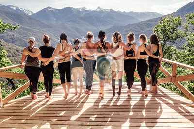 Naklejka Rear view of a group of slim body-positive sportive active friendly women doing fitness and yoga together among mountain ecologically clean nature. Ecological Sports Tourism Concept