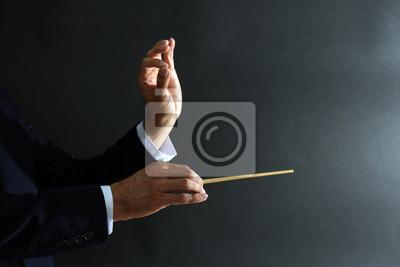 Naklejka Ręce dyrygent Muzyka z batutą na czarnym tle