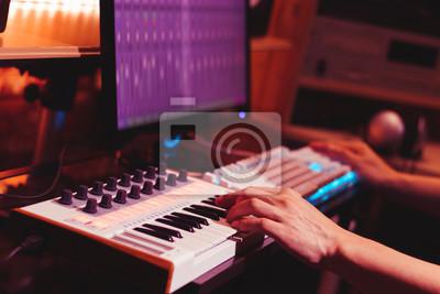 Naklejka Ręce muzyk grający syntezator klawiatury midi do nagrywania muzyki na komputerze w studio dźwięku cyfrowego