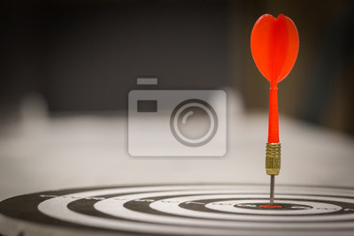 Naklejka Red dart arrow hitting in the target center of dartboard on bullseye with sun light vintage style, Target marketing and business success concept - Image.
